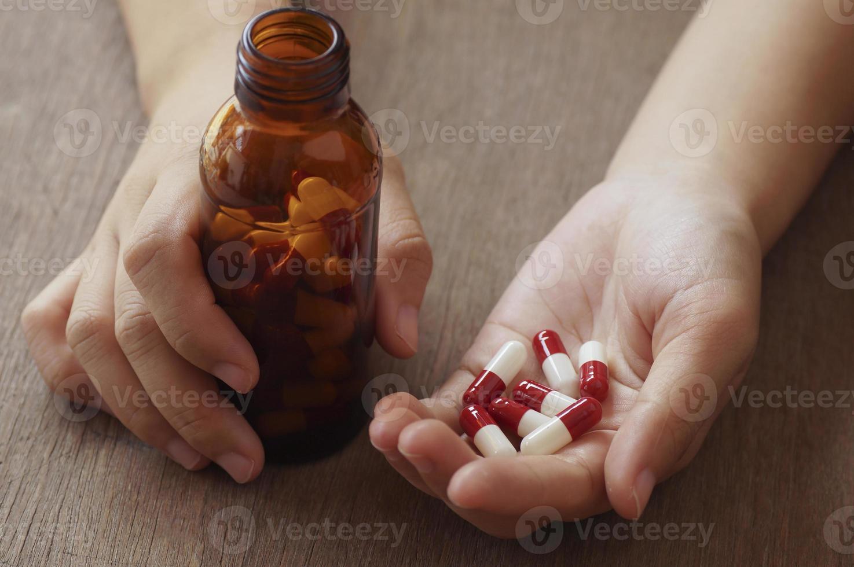 pessoa segurando cápsulas vermelhas e brancas foto