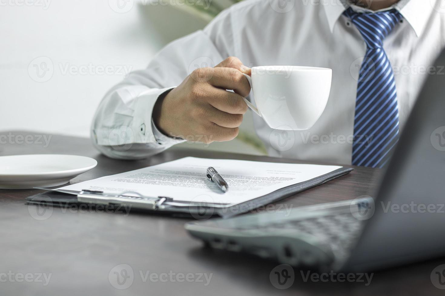 pessoa de gravata segurando uma xícara de café foto