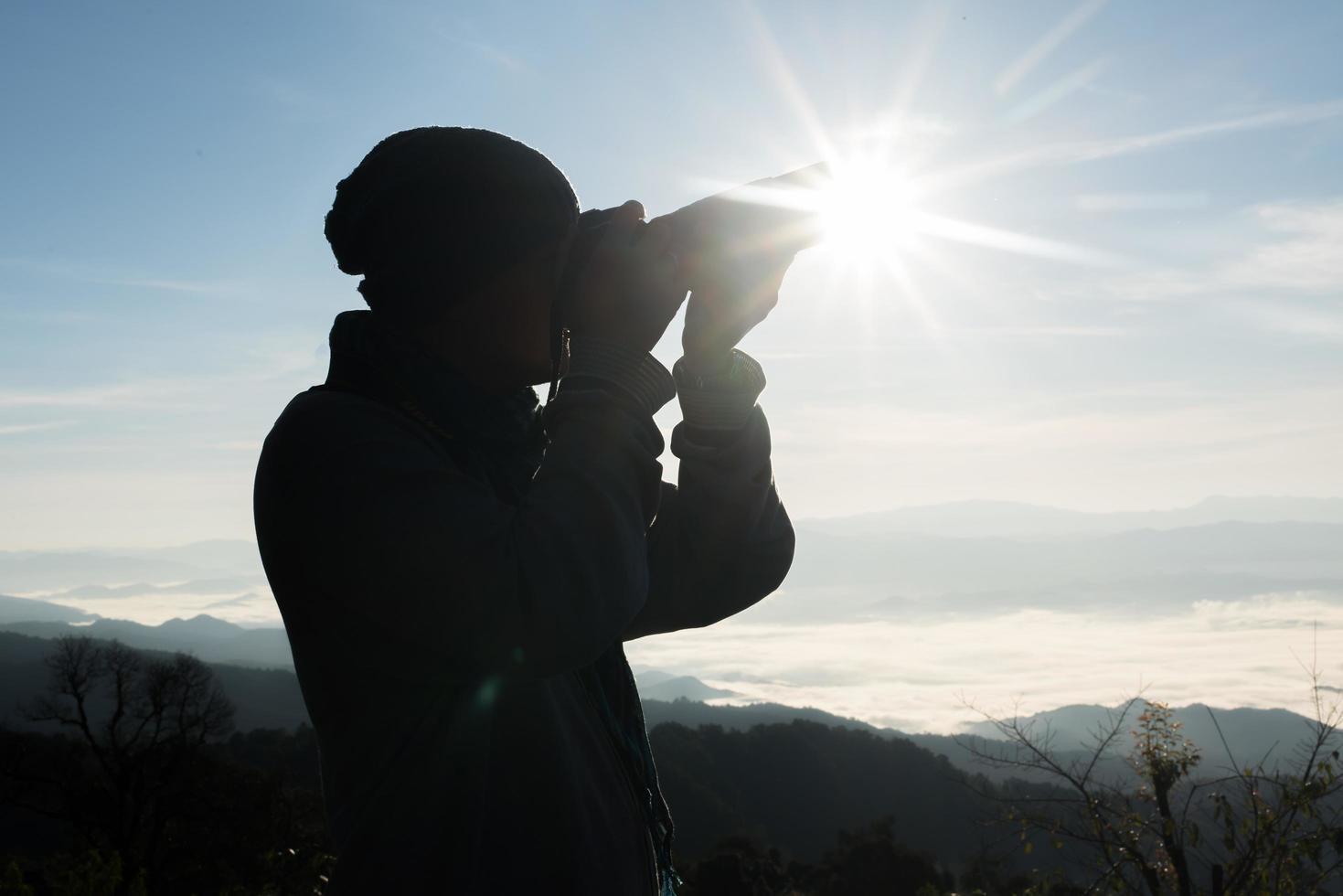 silhueta de jovem fotógrafo segurando uma câmera com paisagem de montanha foto