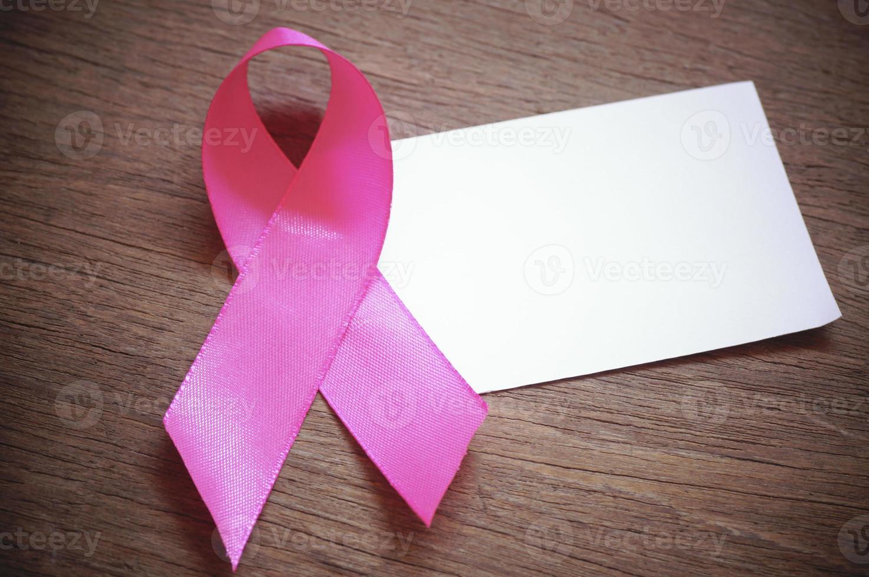 câncer de mama fita rosa com papel branco vazio em fundo de madeira foto