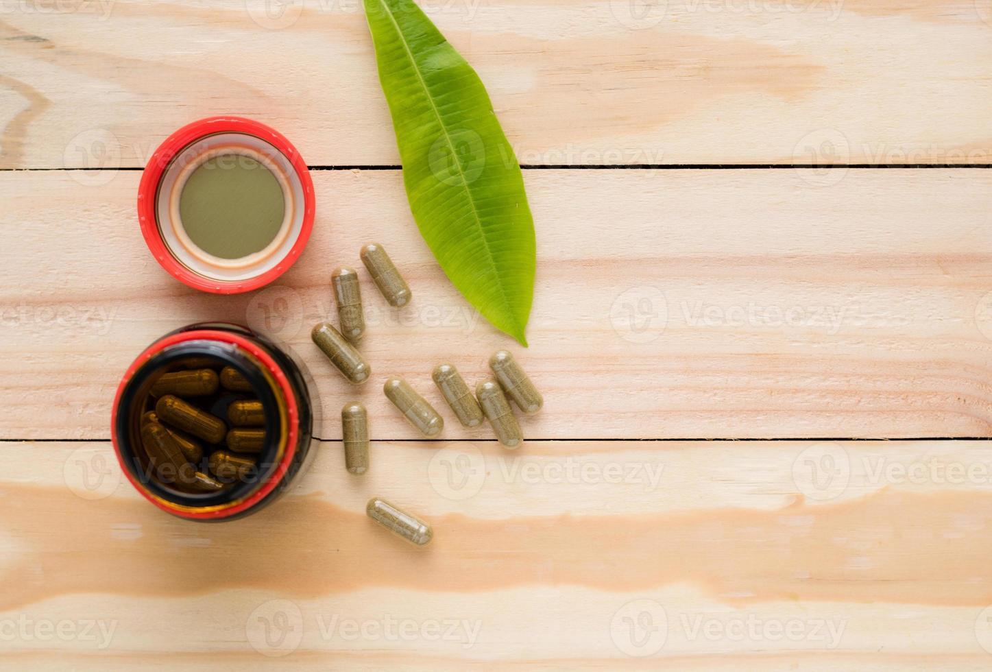 vista superior de cápsulas de medicamentos fitoterápicos e frasco no fundo de madeira foto