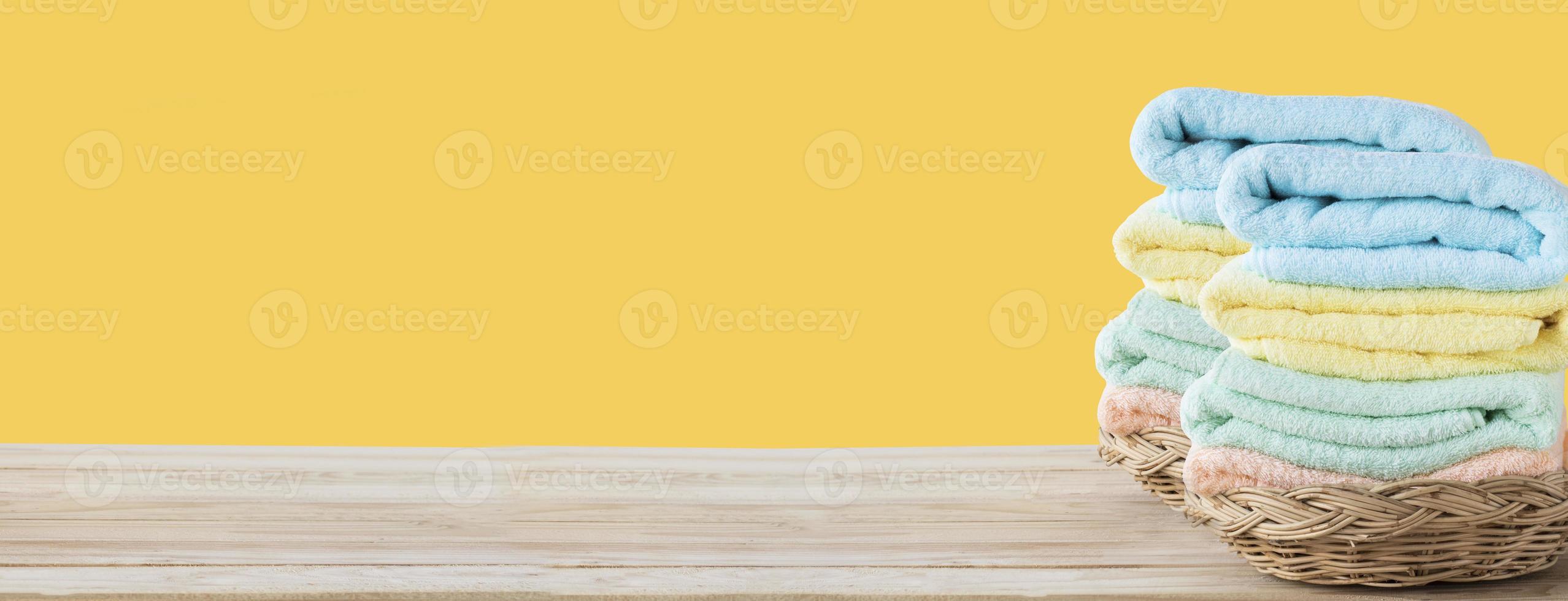 toalhas na cesta na mesa de madeira foto