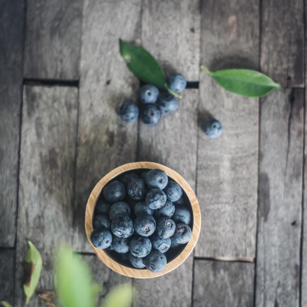 ameixas frescas em uma tigela de madeira com fundo de madeira velho foto