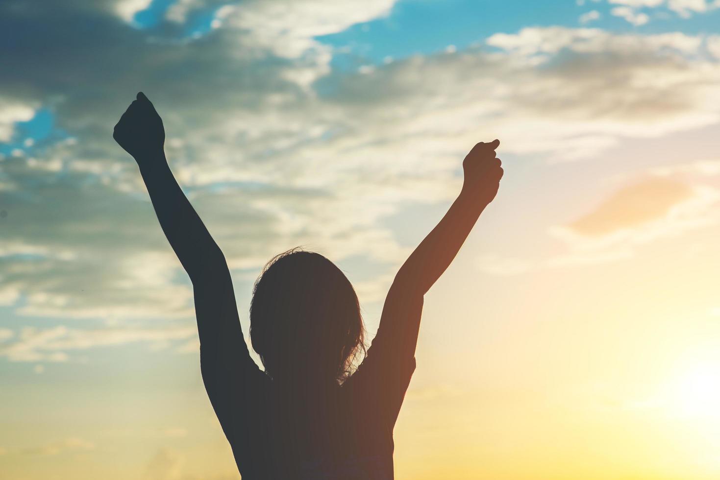 silhueta de uma menina levantando as mãos pela liberdade foto