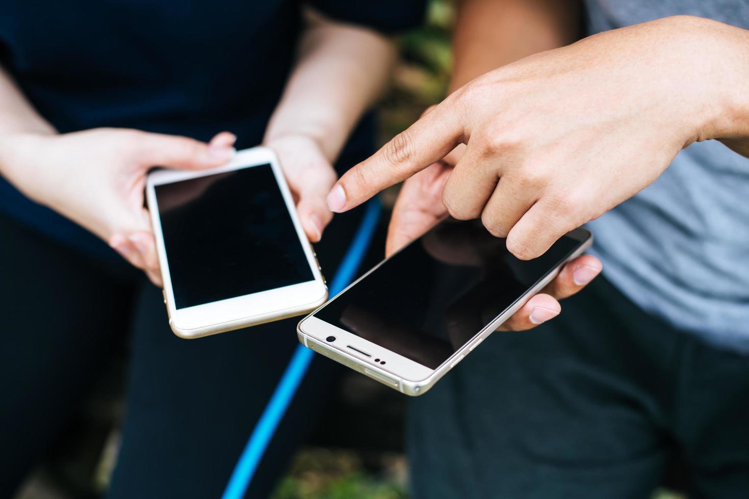 close-up de amigos jogando juntos em smartphones foto