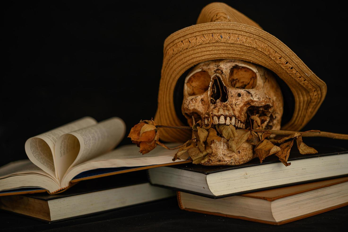natureza morta com um livro em forma de coração e uma caveira com flores secas foto