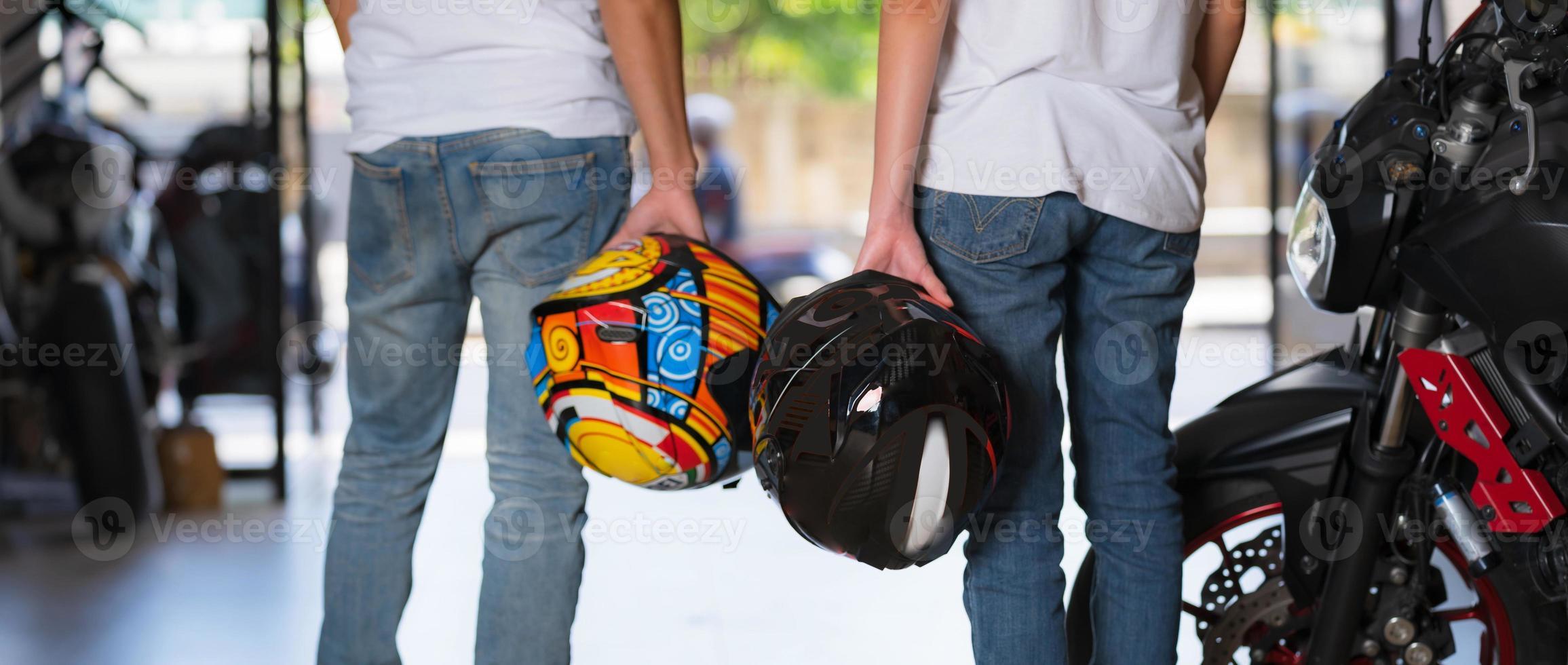 casal de viajantes carregando capacetes de motocicleta foto