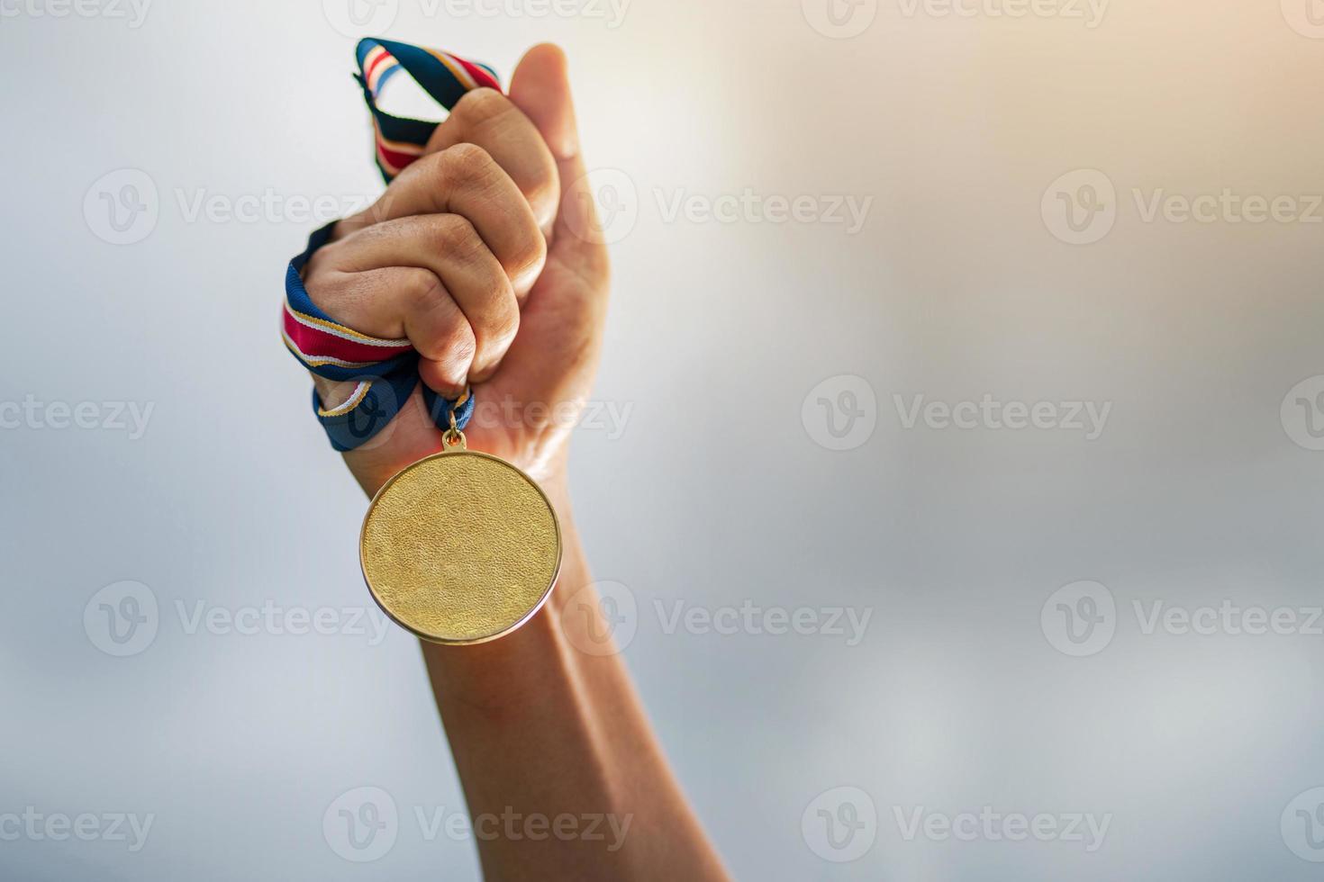 mão segurando uma medalha de ouro foto