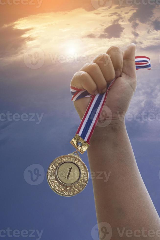 mão segurando a medalha do primeiro lugar foto