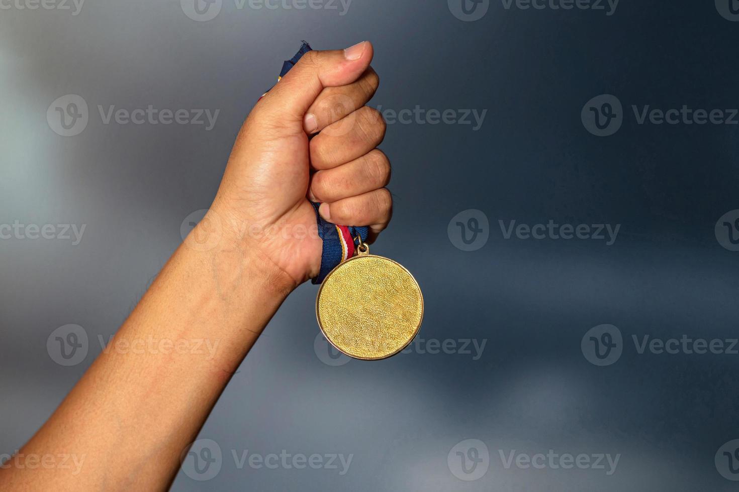 pessoa segurando uma medalha de ouro foto