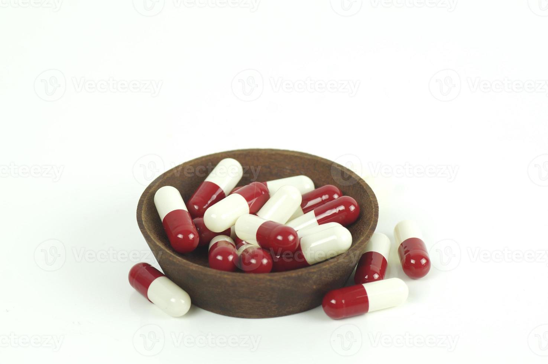 cápsulas vermelhas e brancas em copo de madeira isoladas no fundo branco foto
