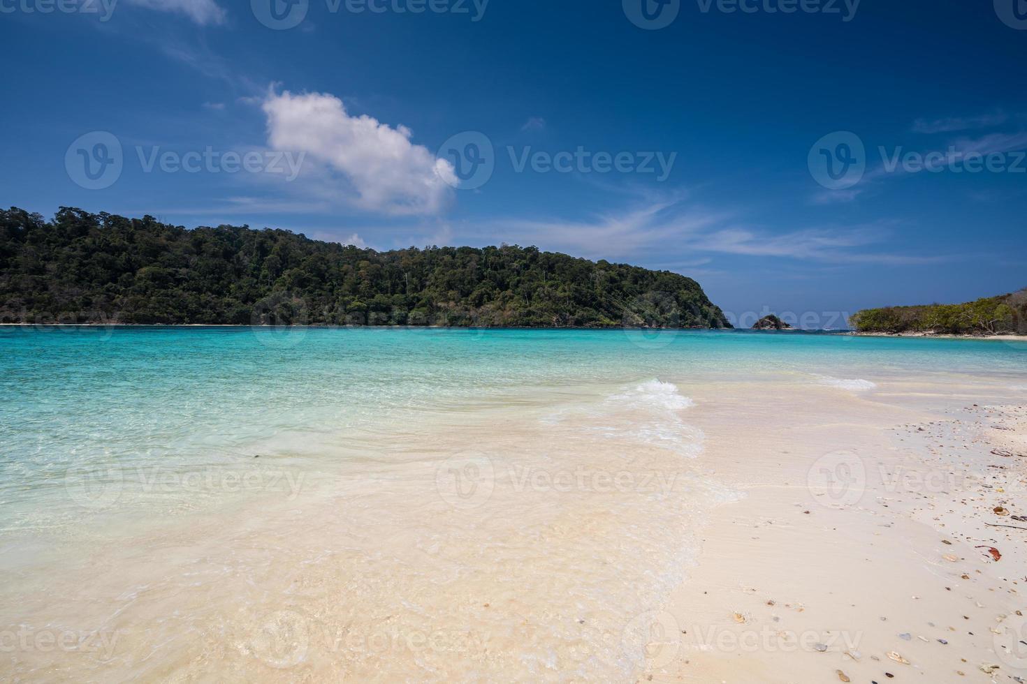 praia de areia branca com água azul foto