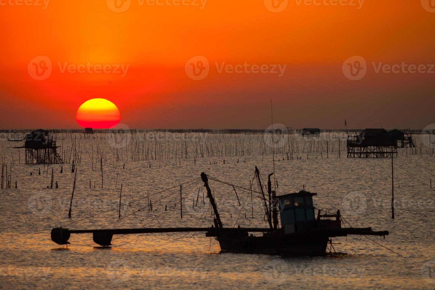 silhueta do barco de pesca e um pôr do sol foto