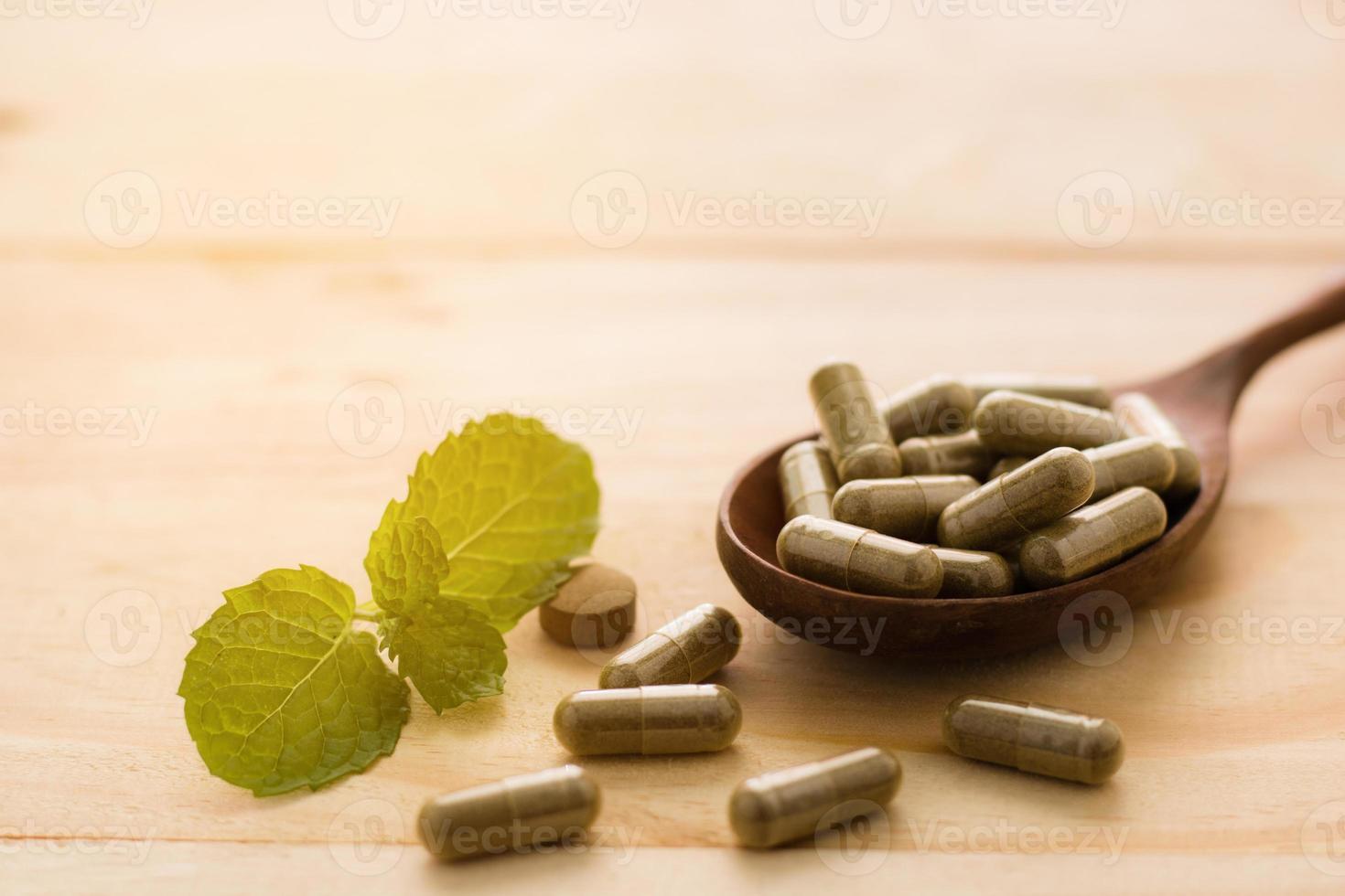droga à base de ervas ou pílula no fundo de madeira foto