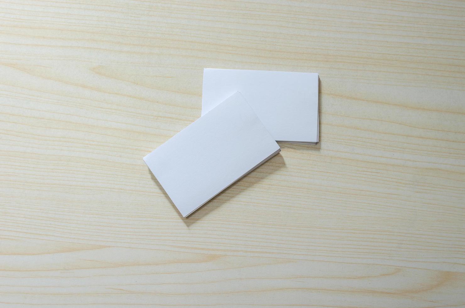 uma maquete de papel em branco para cartões de visita em uma mesa de madeira foto