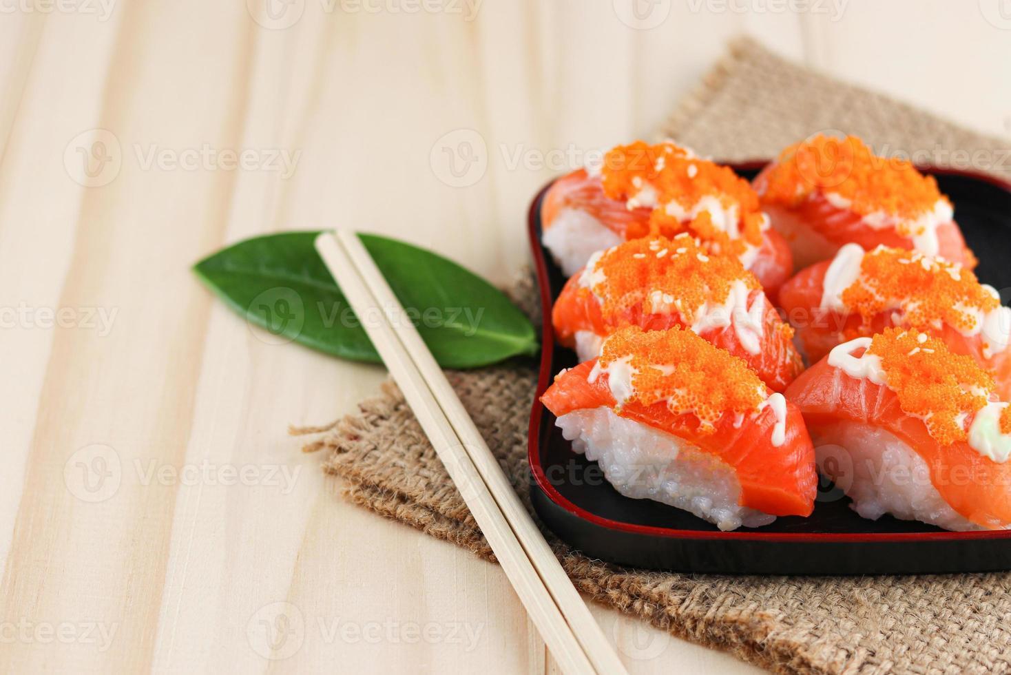 Sushi de salmão na placa preta e tapete de aniagem com pauzinhos na mesa de madeira foto