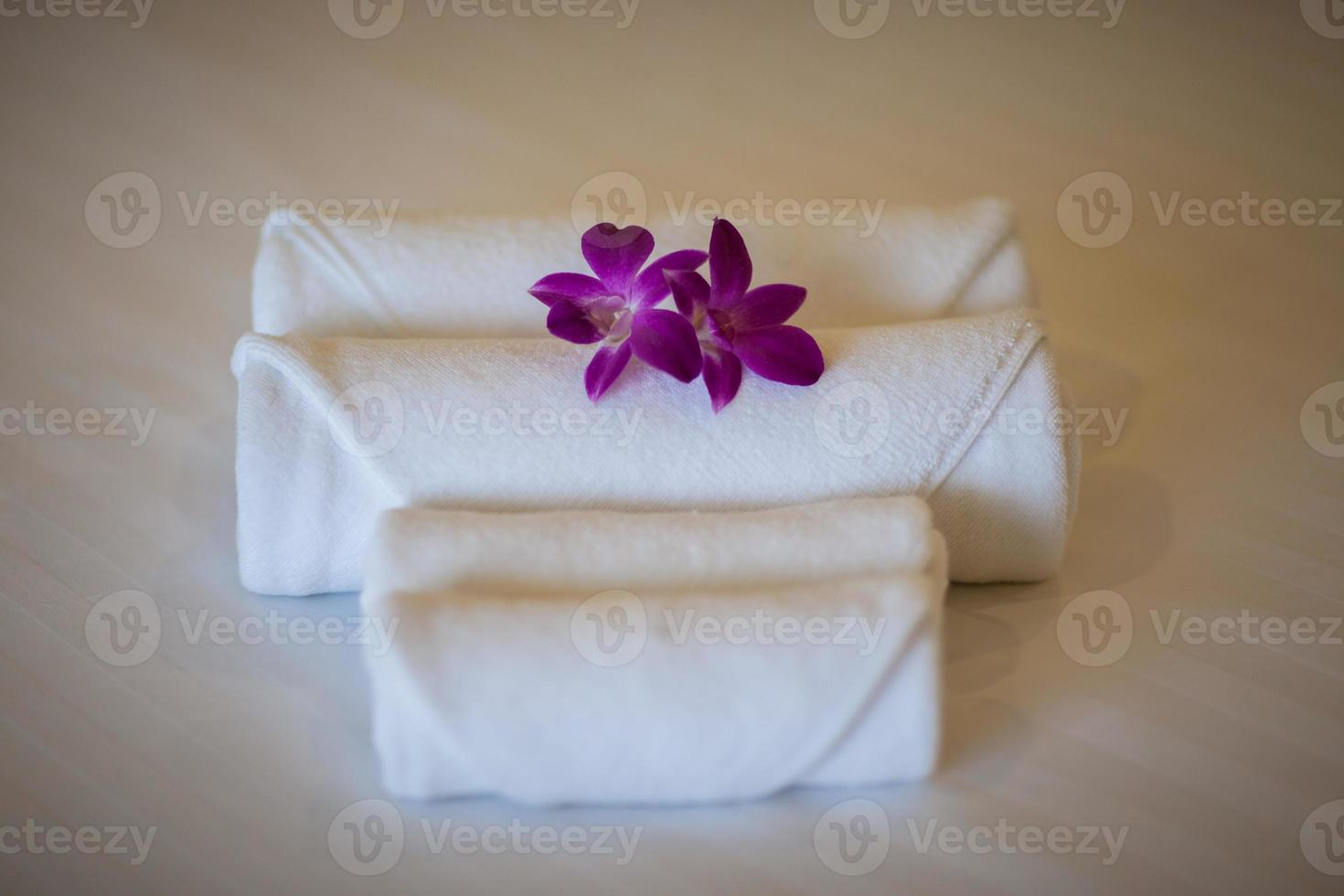 toalhas brancas na cama com flores roxas foto