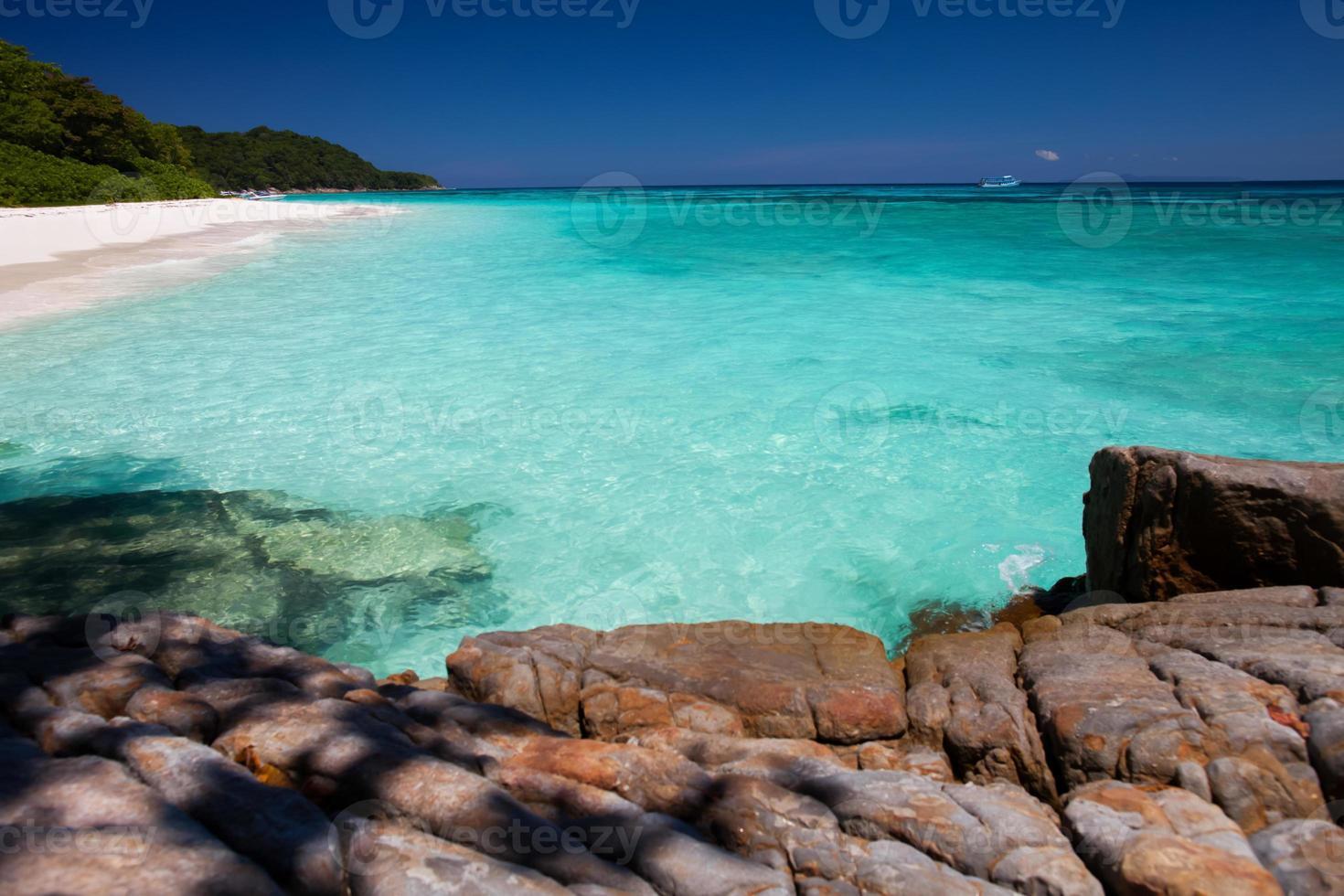 água limpa e pedras na praia foto