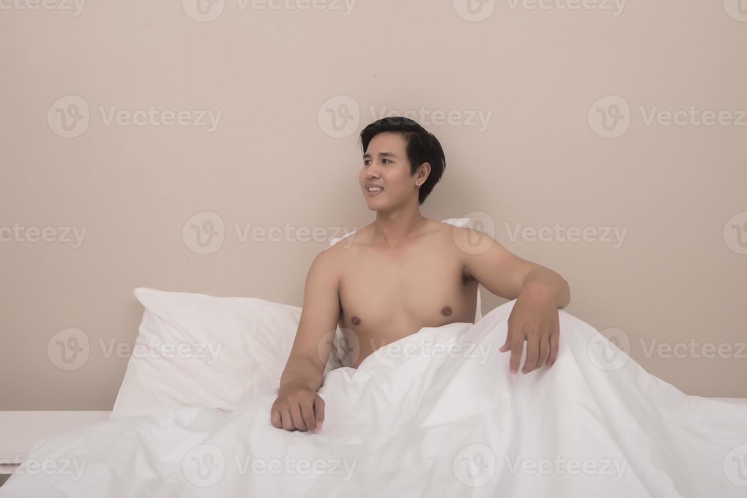 homem bonito acordando na cama foto