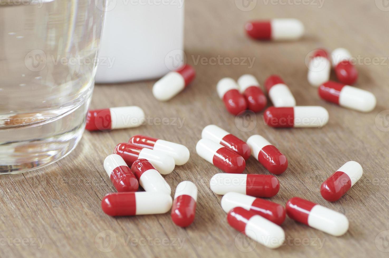 cápsulas vermelhas e copo d'água na mesa de madeira foto