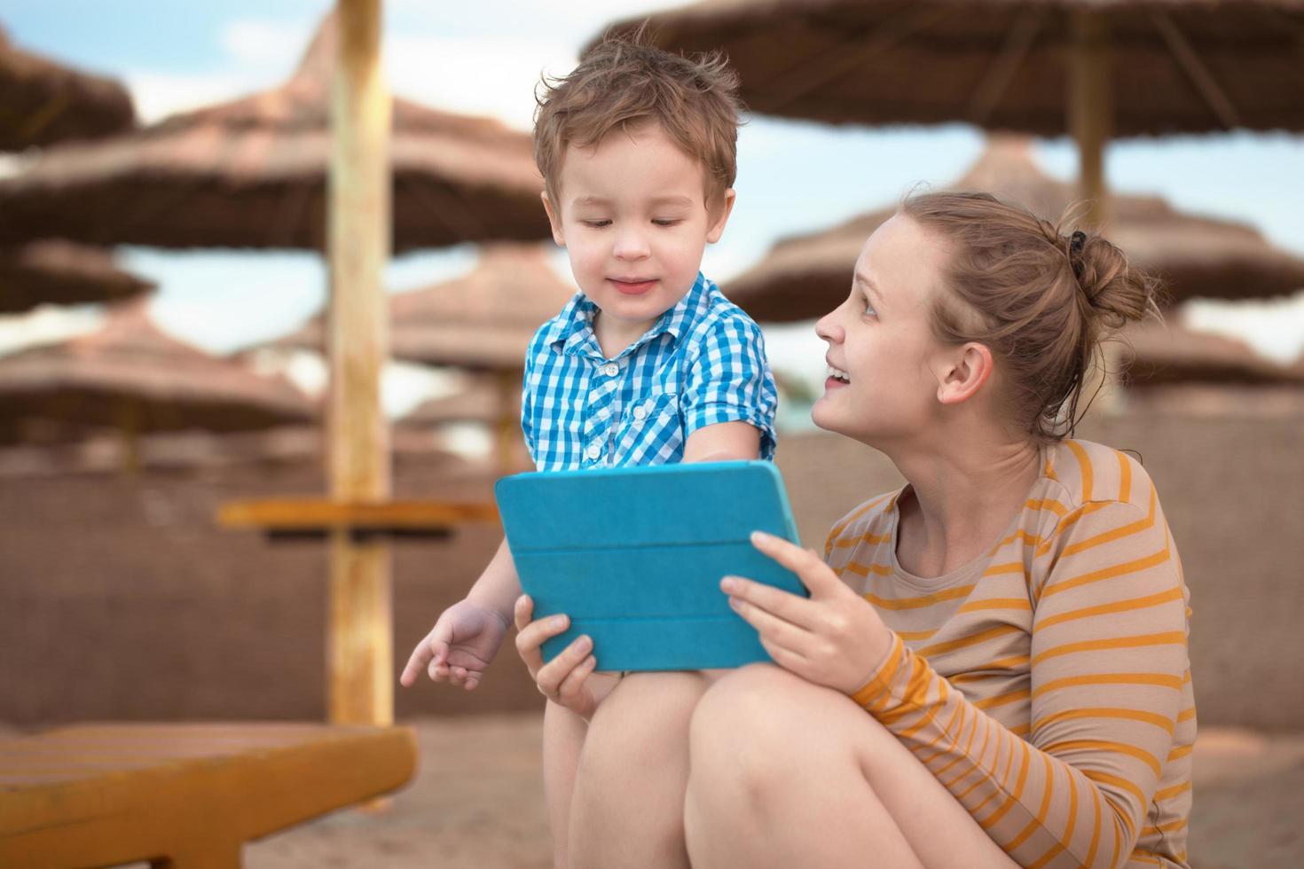 menino e mãe usando um tablet foto