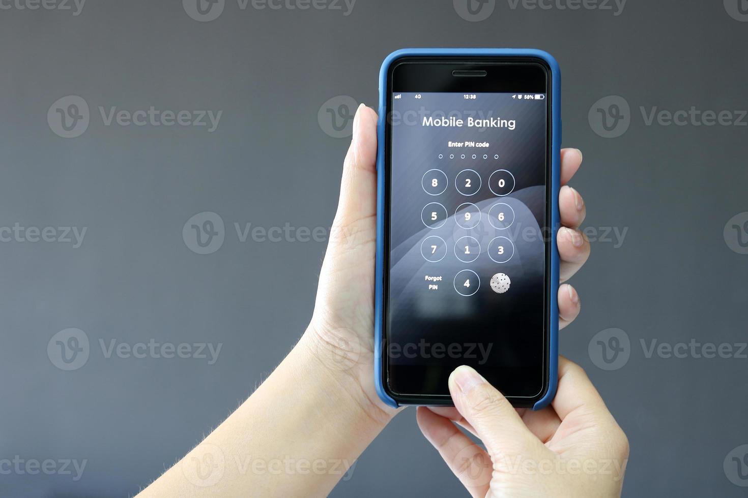 mãos segurando um celular com números de texto de banco móvel foto