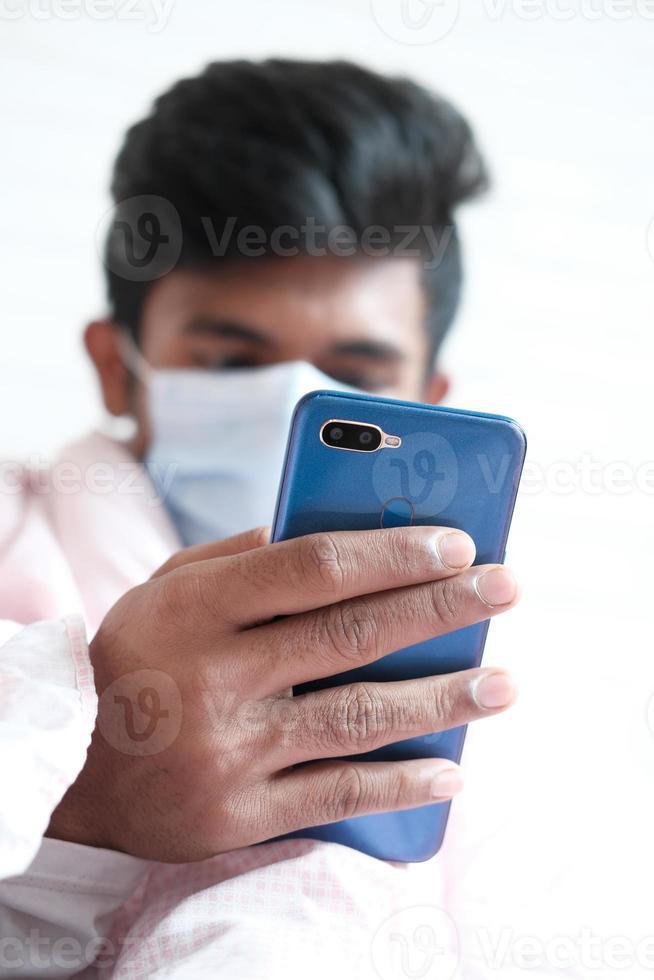 doente com máscara cirúrgica usando smartphone, foco seletivo foto