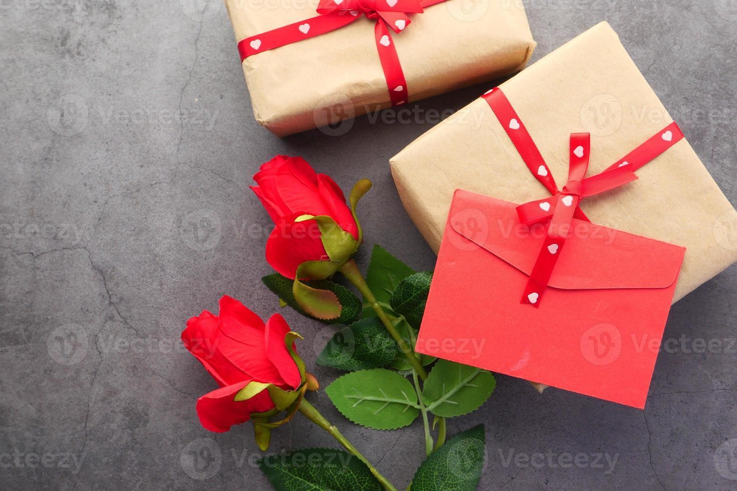 vista superior do envelope do dia dos namorados e flor rosa em fundo preto foto