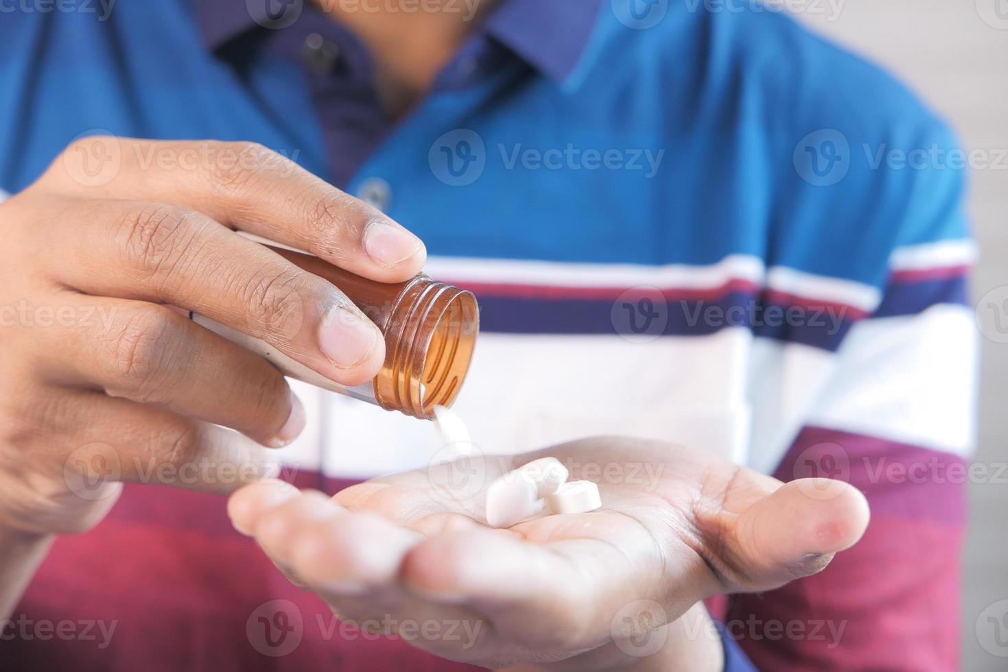 a mão do homem com o remédio derramado do recipiente do comprimido foto