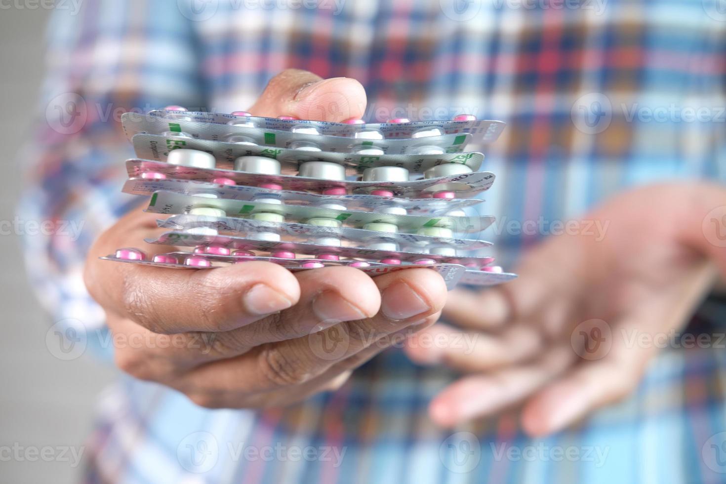 close-up de uma mão segurando embalagens de remédio foto