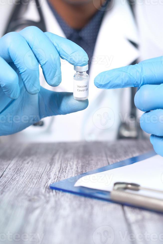 mão em luvas de látex segurando vacina contra coronavírus, com espaço de cópia foto