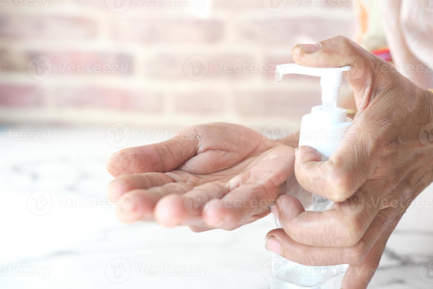 close-up de mulher idosa usando gel desinfetante para as mãos para prevenir vírus foto