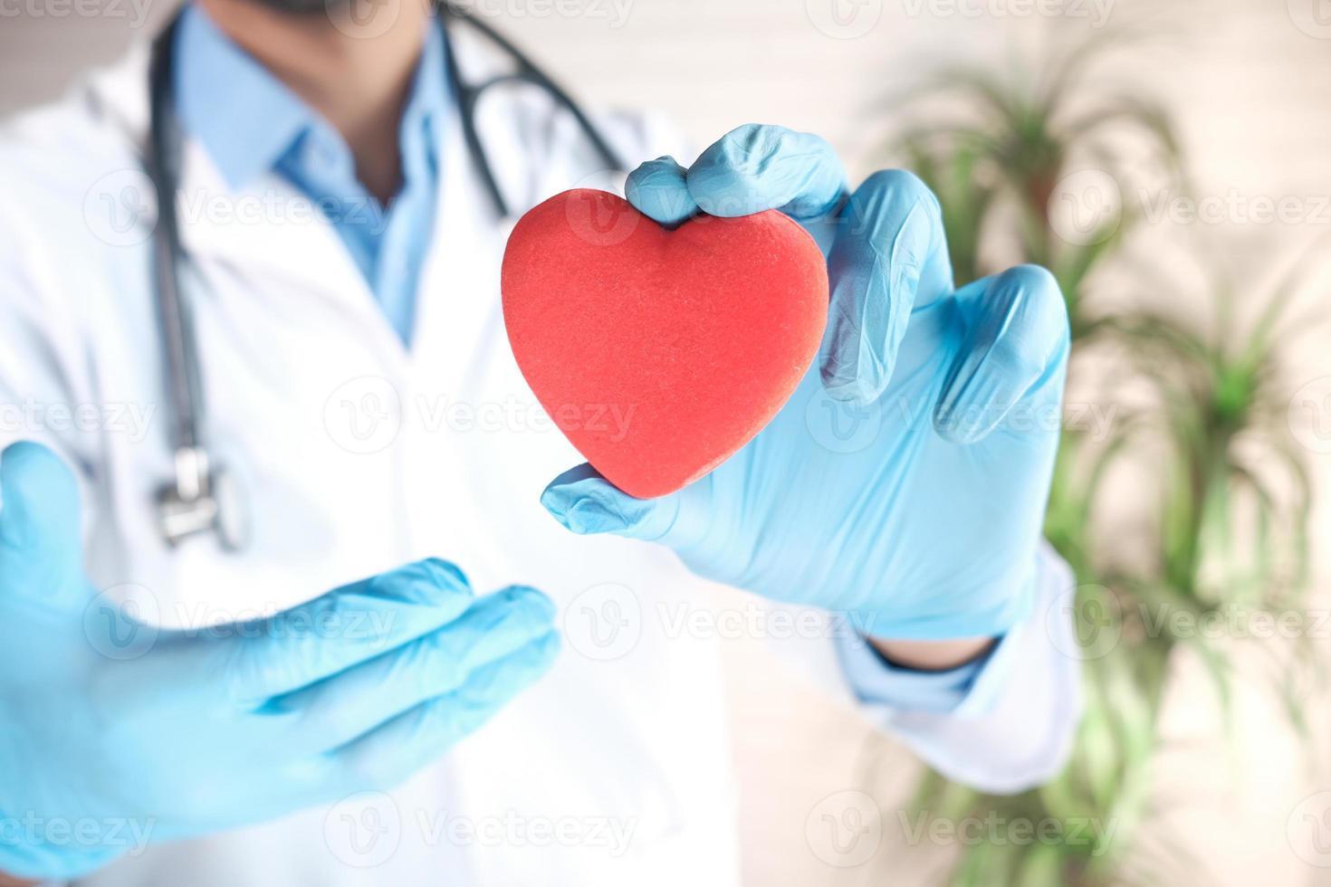 mão do médico em luvas de látex segurando um coração vermelho de perto foto