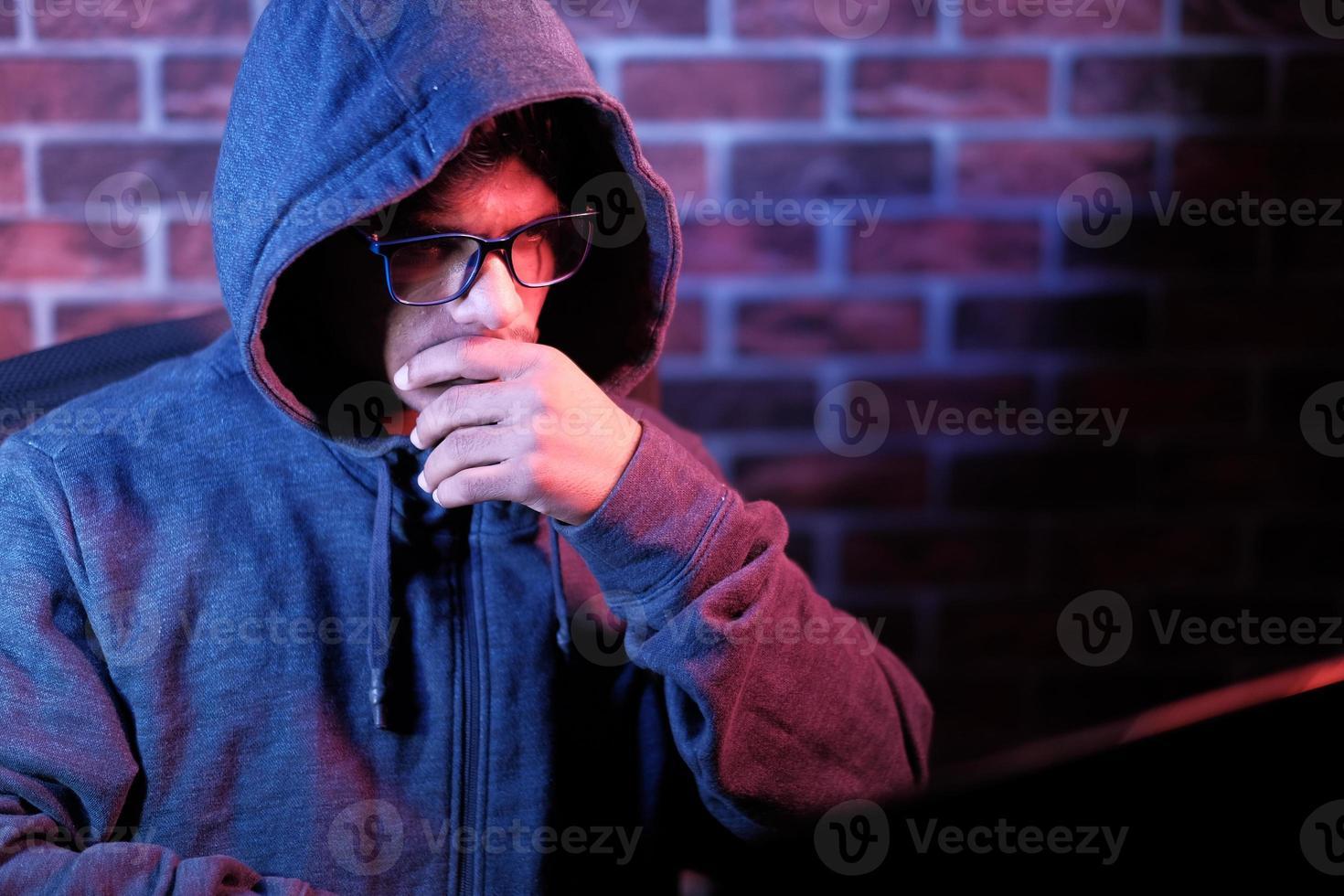 homem encapuzado trabalhando em um laptop foto