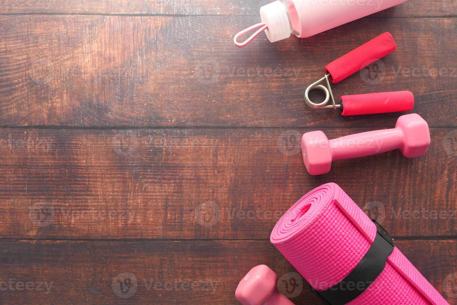 equipamento de fitness rosa em fundo de madeira foto