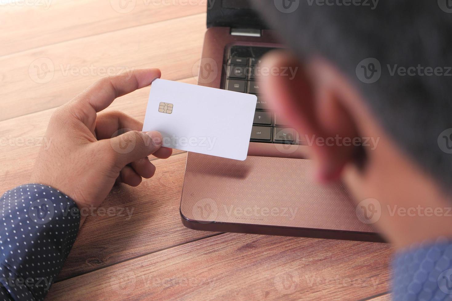 homem segurando um cartão de crédito e fazendo compras online foto