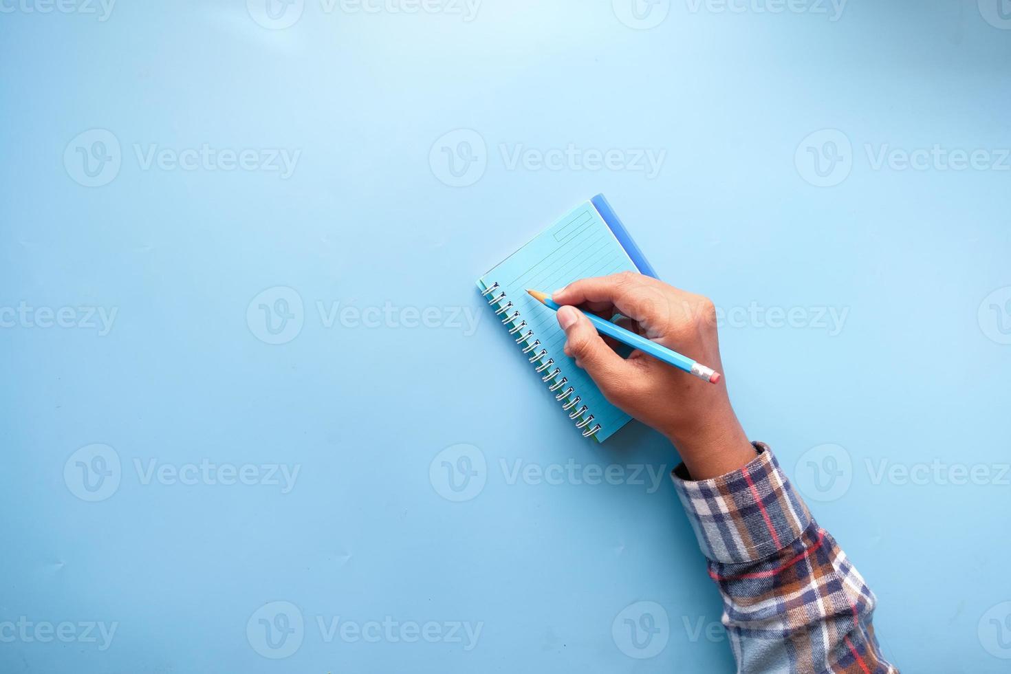 a mão do homem escrevendo no bloco de notas sobre fundo azul foto