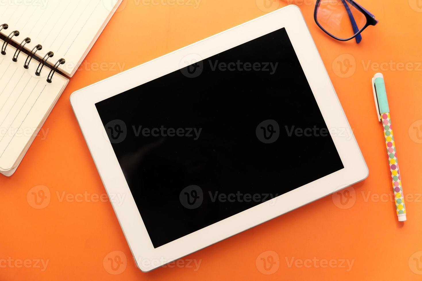 composição plana de tablet digital e escritório estacionário em fundo laranja foto