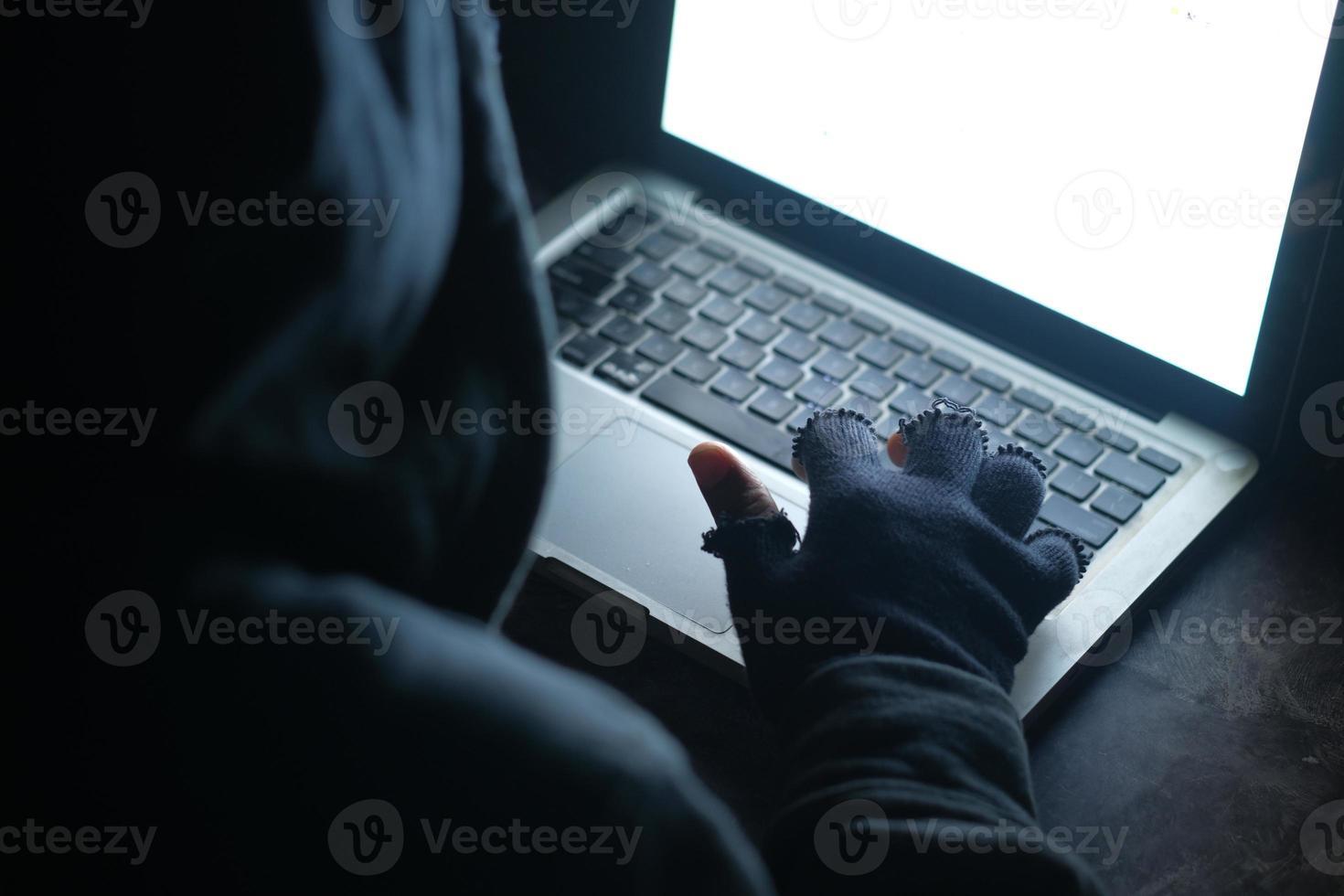 homem encapuzado roubando dados de laptop foto