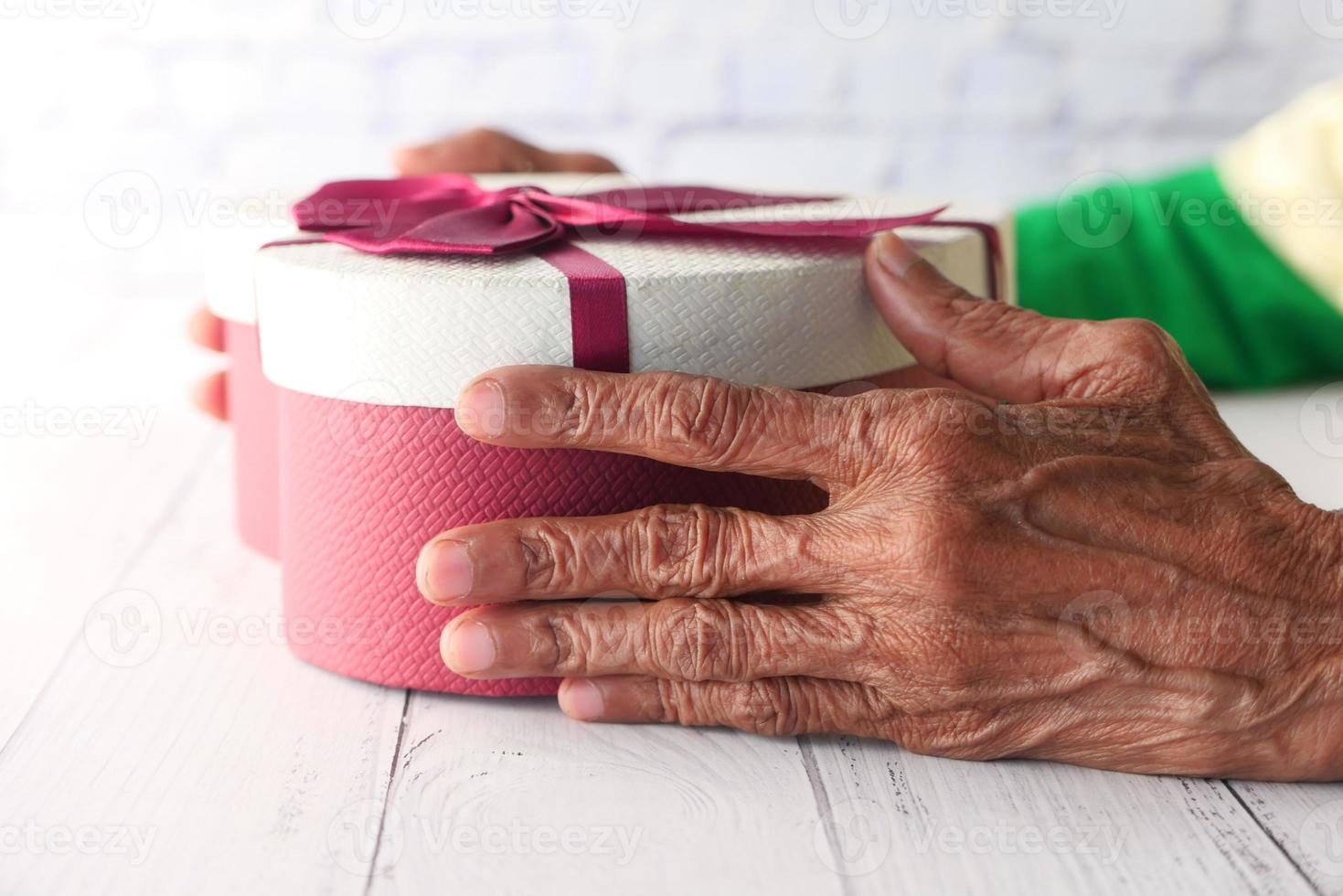 mãos de uma mulher idosa segurando uma caixa de presente em forma de coração foto