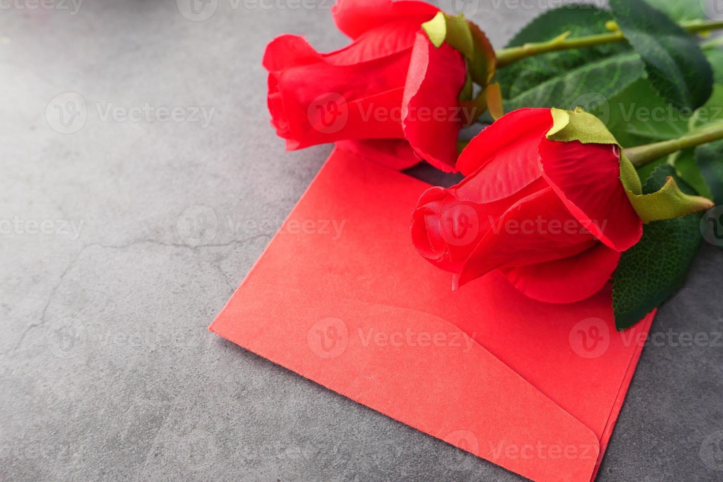 envelope vermelho e rosas vermelhas foto
