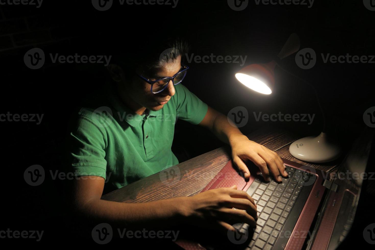 homem trabalhando em uma mesa à noite foto