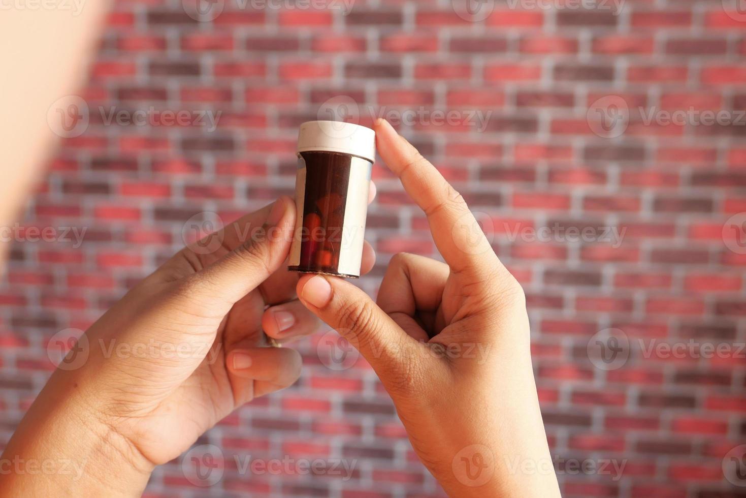 homem segurando um frasco de comprimidos foto