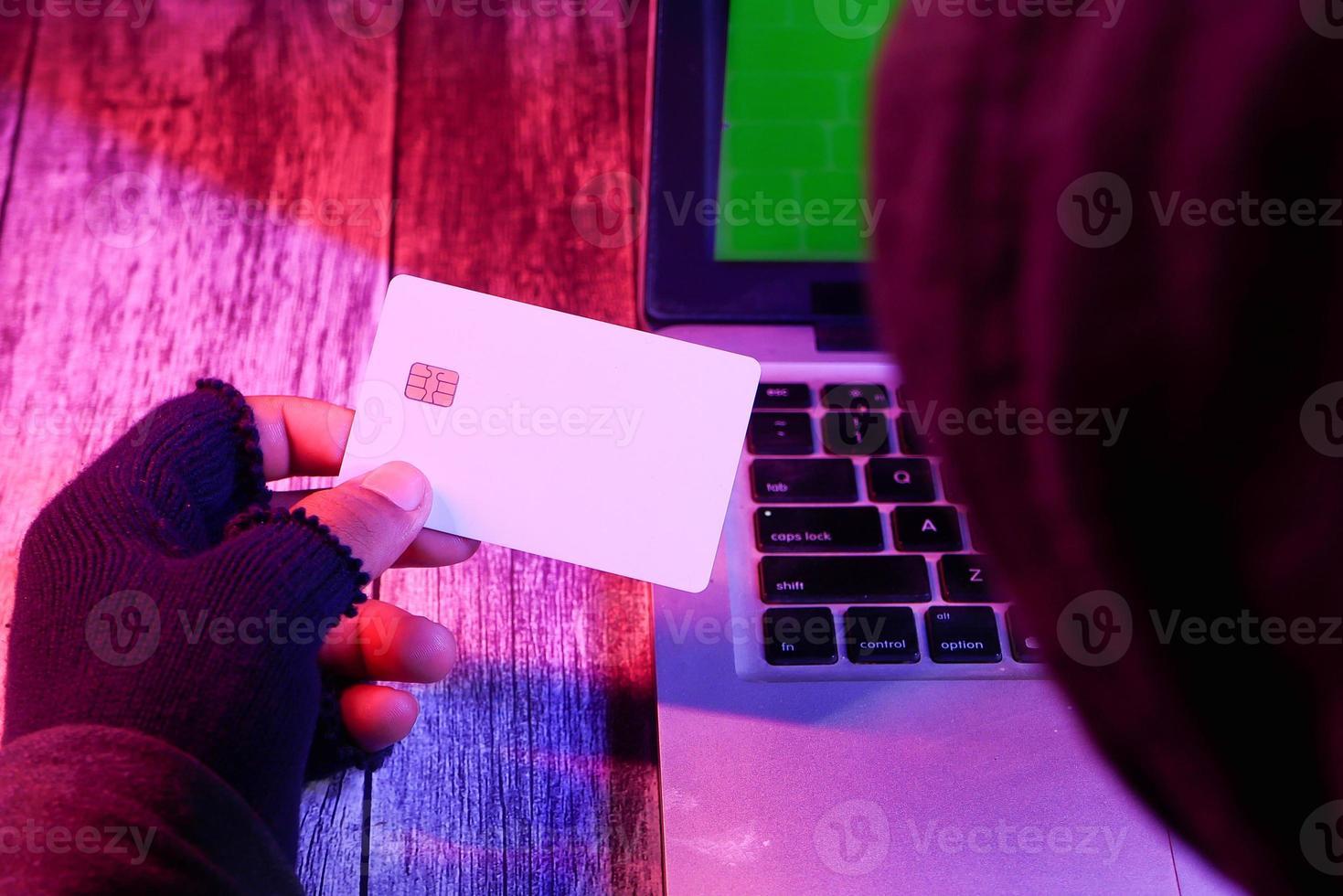 mão do hacker um cartão de crédito foto