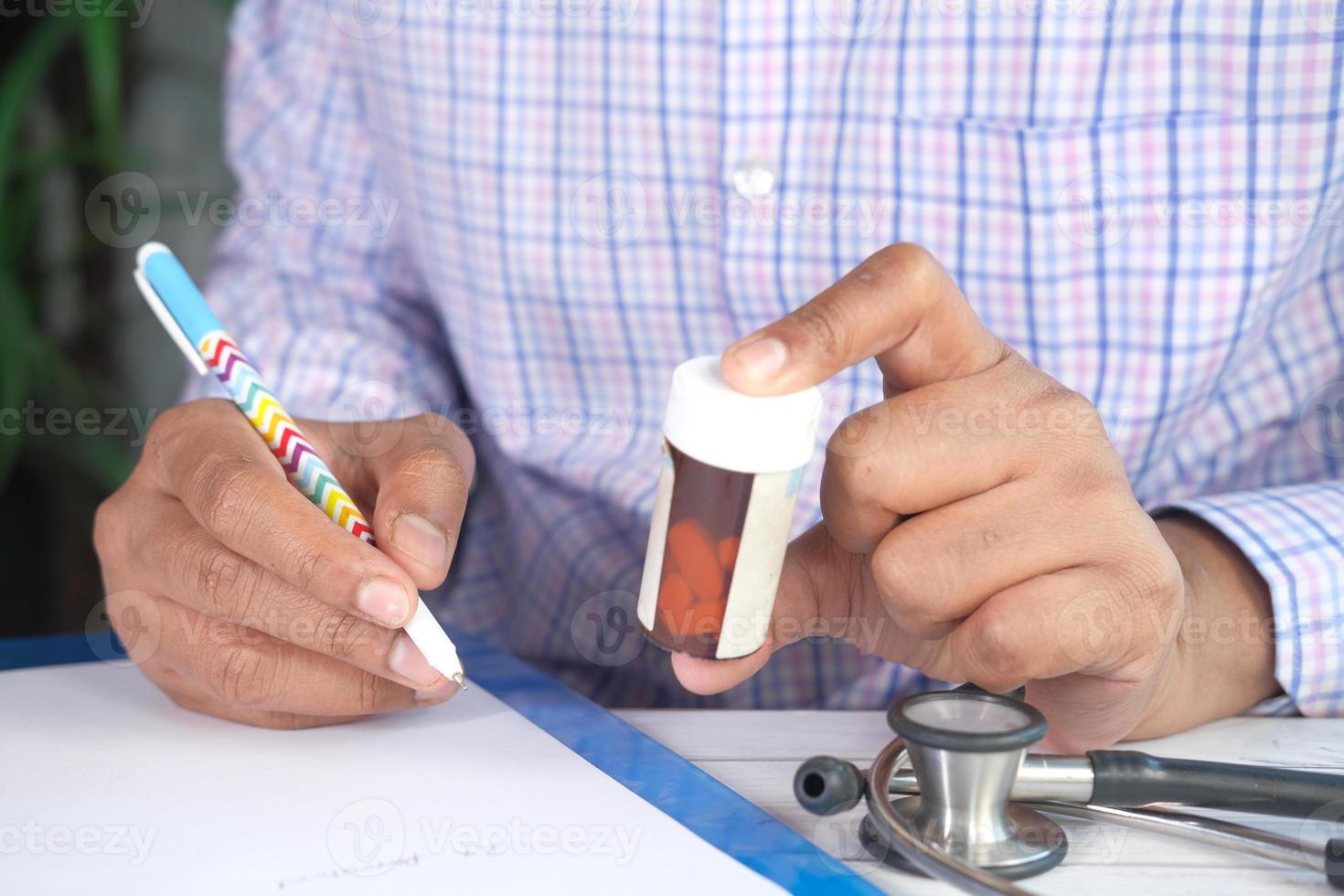 mão do médico escrevendo a receita na mesa foto
