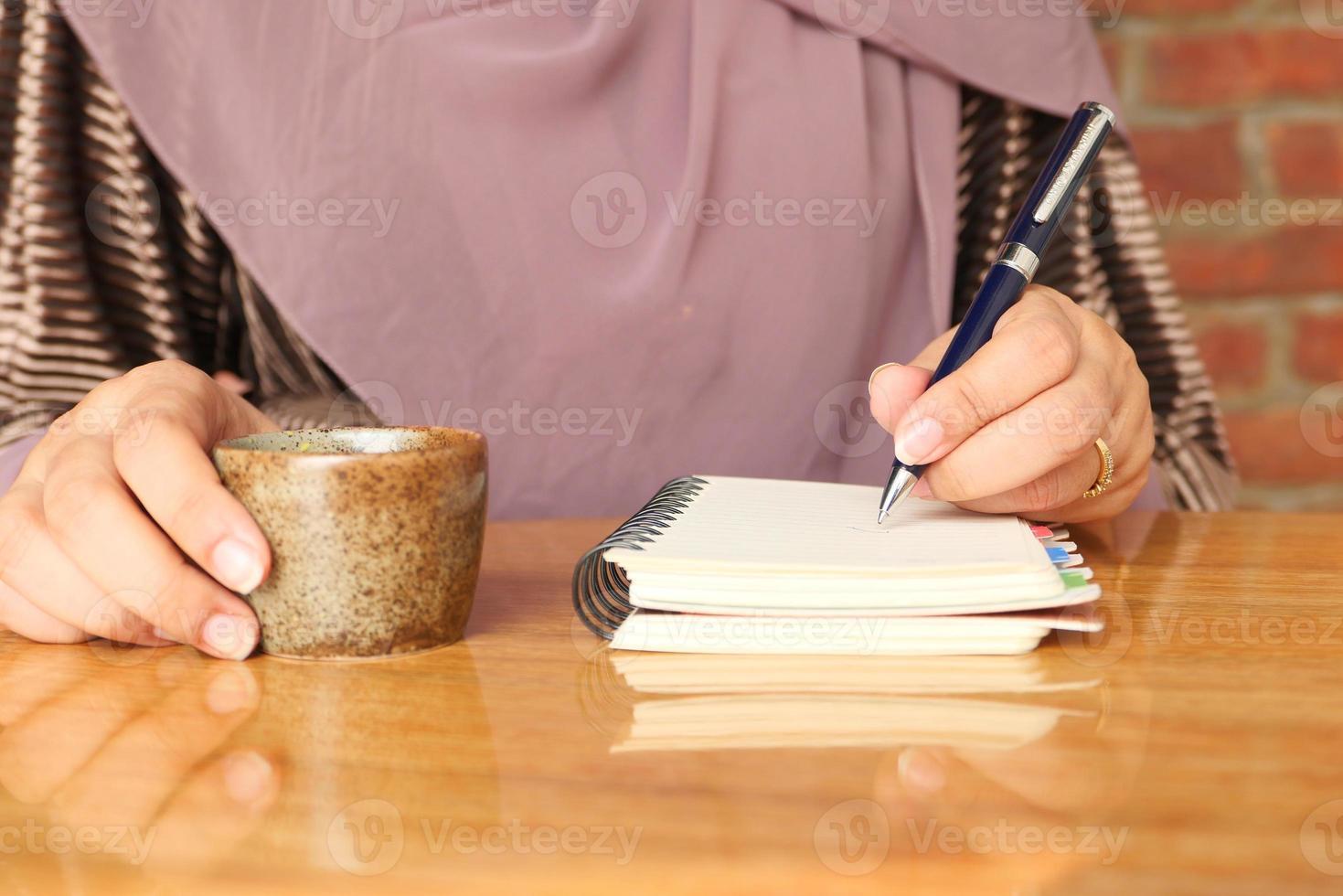 perto da mão de uma mulher escrevendo no bloco de notas foto