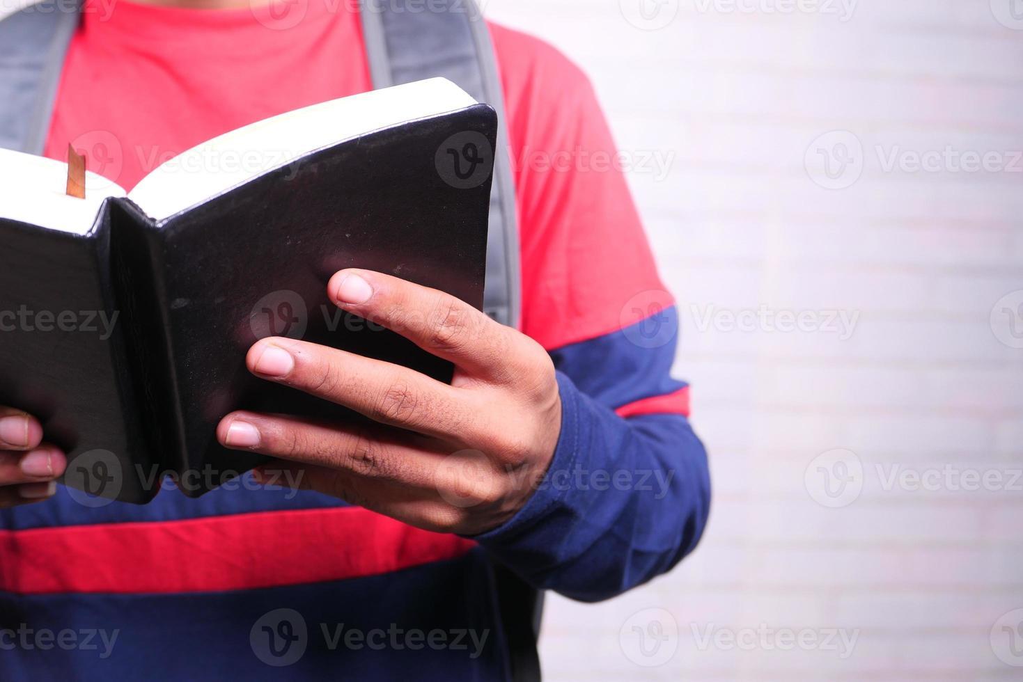 homem lendo um livro preto foto