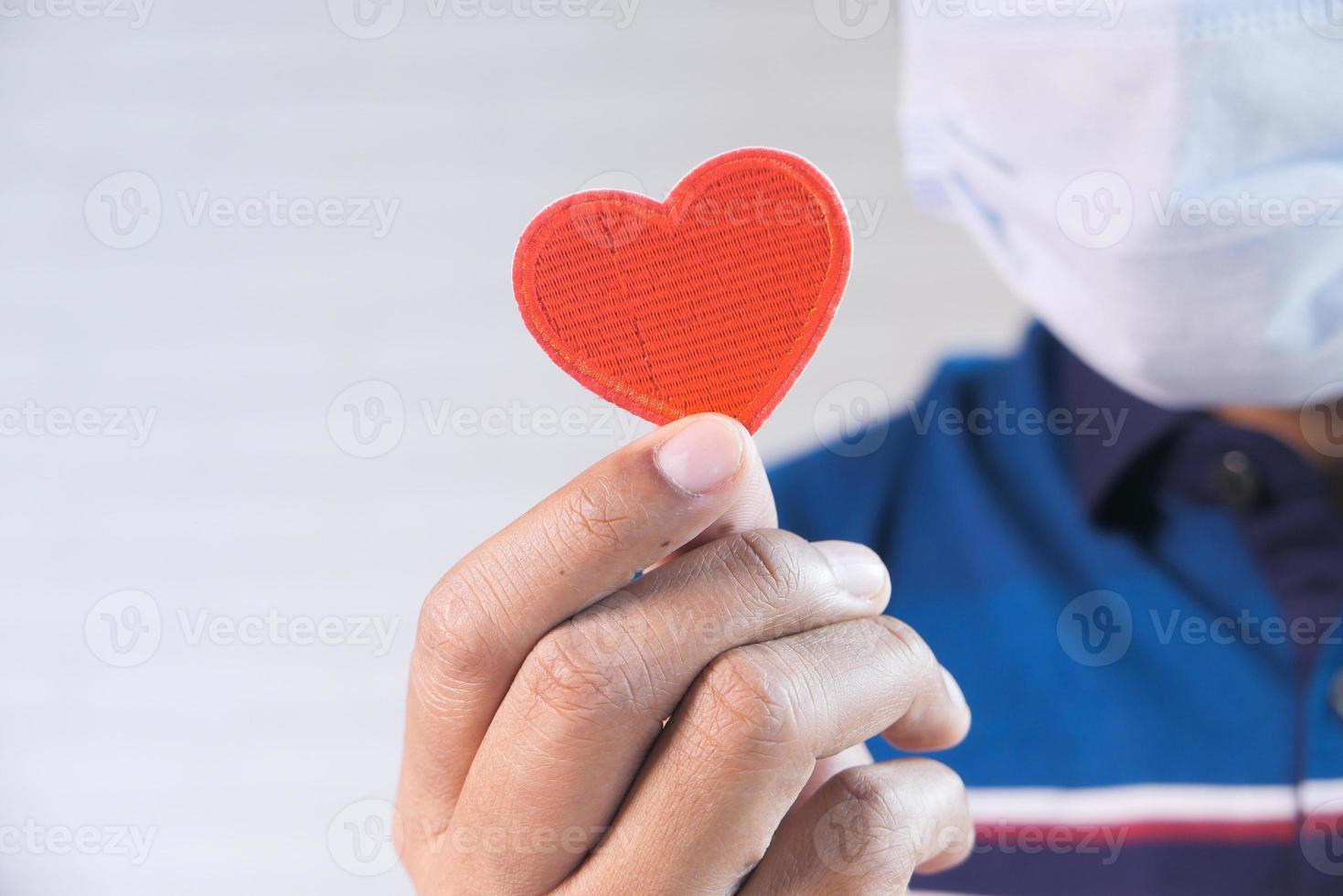 mão segurando coração vermelho foto