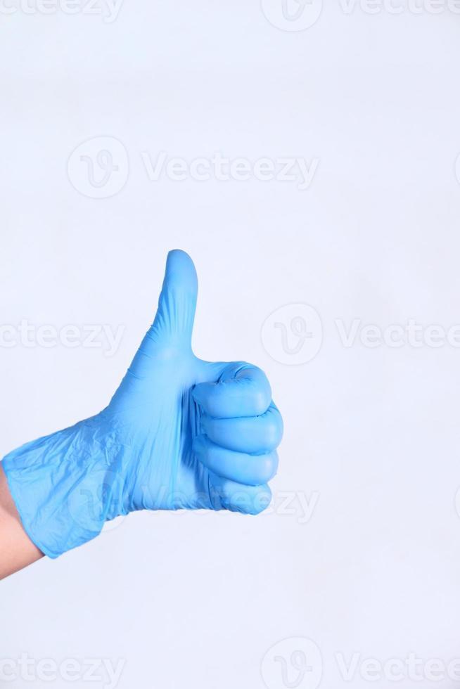 polegares para cima usando luva azul em fundo branco foto