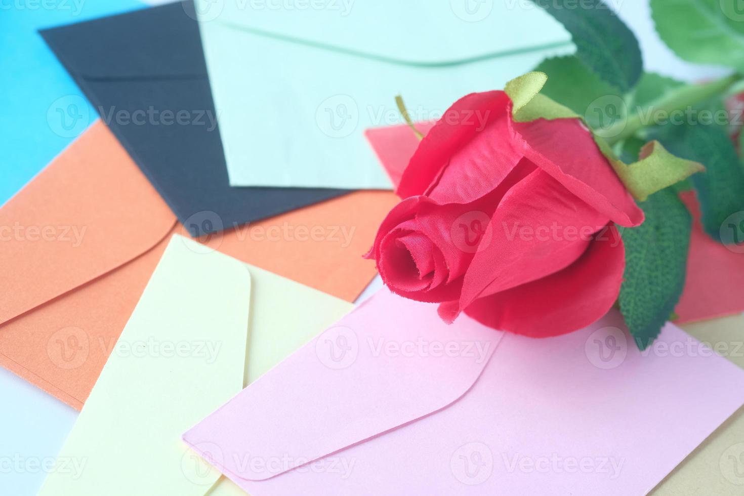rosa artificial com envelopes coloridos foto